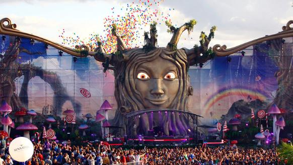 Chủ đề TomorrowLand 2011 với visual sân khấu khuôn mặt mở to mắt có những chiếc rễ cắm sâu xuống đất